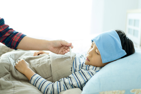 termometer: Young boy sleeping and sick on the bed with cooler gel on his head. and take care by his mom hand measuring temperature by little thermometer. Stock Photo