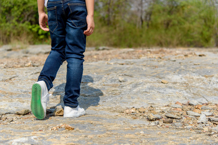 Kids in blue jean walking through the rough rocky land in the day time with strong sunlight. focus on shoe. Stock Photo