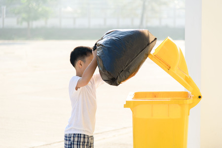 sunligh: Young Asian boy carry garbage in plastic bag for eliminate in the yellow bin under the sunligh