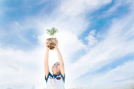 Warm tone, young asian boy lift little plant to the sky. Earth day concept