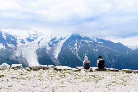 Selective focus at Young Japanese tourist looking to beautiful View of Mont Blanc Massif with the grass and little flower as forground,Chamonix,France