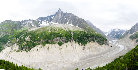 glace: Panorama of Drus , Mer de Glace glacier and Grandes Jorasses in the Mont Blanc massif during the cloud and rainy day in summer at Chamonix, French Alps