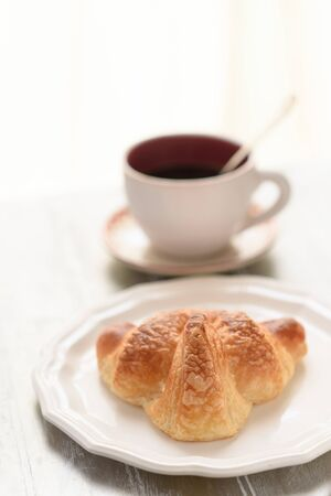 Selective focus on croissant brown skin. A fresh croissant on the white plate beside a cup of coffee on the wooden table.