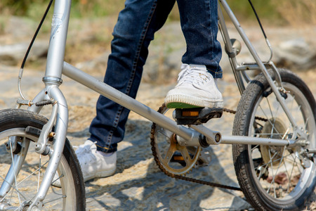 rough road: Selective focus at leg and shoe of Young boy wear blue jean ride an vintage color old bicycle on the stone rough road on the dry hill in summer time with strong sunlight. Stock Photo