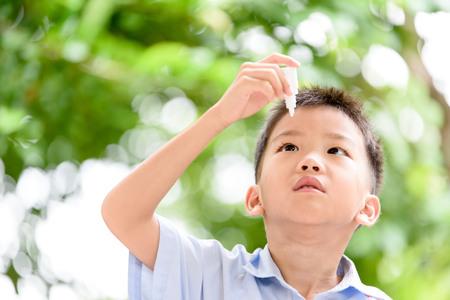 eyedropper: Young Thai boy using eyedropper to cure his eyepain.