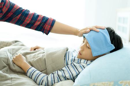 寝ていると彼の頭の上のクーラーのゲルとベッドに病気の若い男の子。彼のお母さんの手で世話をして 写真素材