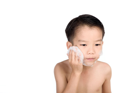 Young boy put foam on his face before shaving in the bathroom.