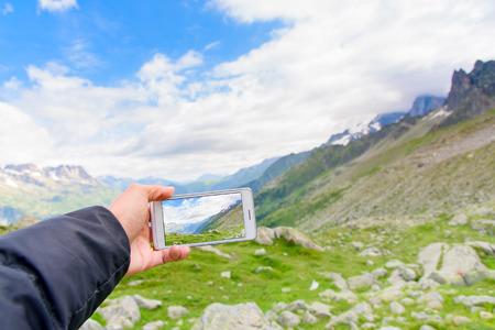 Hand holding smartphone taking photo of Aiguile du Chardonnet a beautiful view of Mont Blanc Massif , Chamonix France, Europe