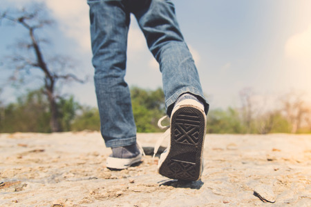 Vintage color, Kids leg in blue jean walking through the rough rocky land in the day time with strong sunlight. focus on shoe. Stock Photo