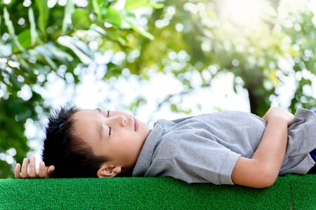 lay down: Young Asian boy lay down on the green lawn in the park during summer season with green bokeh
