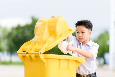 Young Thai student boy in school uniform trow the garbage in the yellow bin.