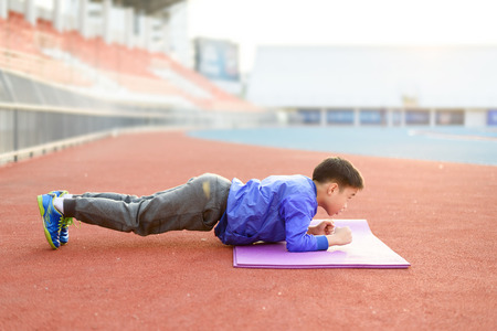 Slim athletic Blue jacket Asian boy doing planking exercise in the stadium during the sunrise.