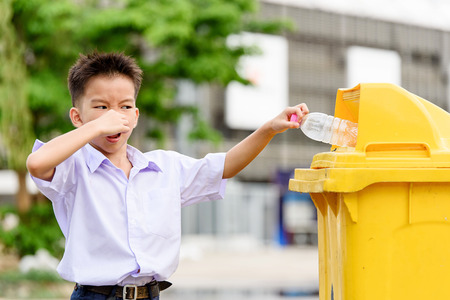 trash the dress: Young Thai student boy in school uniform trow the garbage in the yellow bin and he show bad smelling. Stock Photo