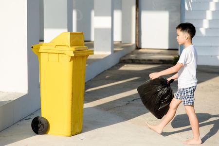 Sunligh の下で黄色の箱の中のビニール袋でアジアの若い男の子を運ぶゴミを排除します。