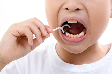 toothpick: Close up Young asian boy useing toothpick to clean his teeth on white background. Stock Photo