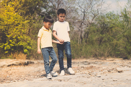 cross legs: Vintage color, Two Boy walking through the rough rocky land in the day time with strong sunlight.