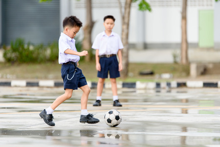 rainfall: Boys in Thai student uniform black shoe play football on the concrete floor after the rainfall with the reflection. Stock Photo