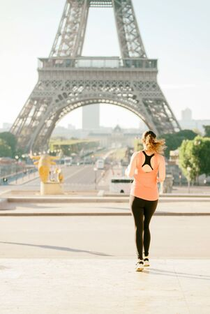 Warm tone of Selective focus at woman running infront of tour Eiffel in the morning. Eiffel tower is the most visit in Paris, France.
