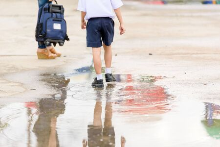 kid book: Young Thai student boy in school uniform walk on the water to his mother
