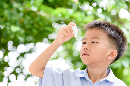 Young Thai boy using eyedropper to cure his eyepain.