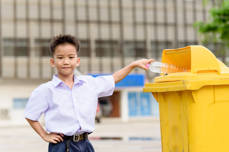 trash the dress: Young Thai student boy in school uniform trow the garbage in the yellow bin.