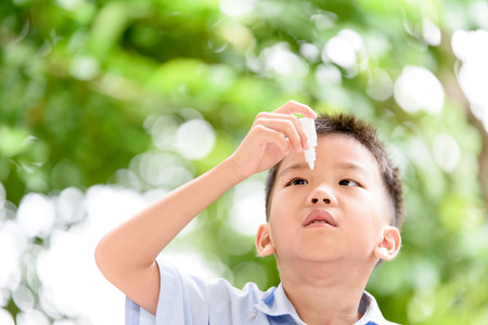 eyedropper: Young Thai boy using eyedropper to cure his eyepain.