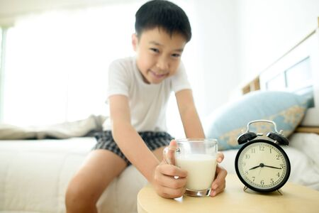 Selective focus on the glass of milk in the bed room taking by the young asian boy. Stock Photo