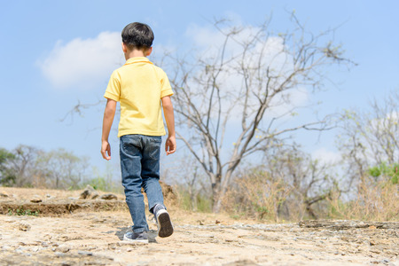 Young Asian Boy walking through the rough rocky land in the day time with strong sunlight.
