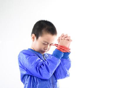 Boy Hände in der blauen Jacke dicht sind durch rote Nylonseil auf weißem Hintergrund. Freiheit Konzept.