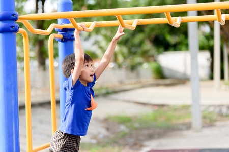 Young asian boy hang the yellow bar by his hand to exercise at out door playground