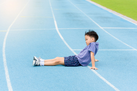 Selective focus at young Asian boy sit and tired on blue track after running.