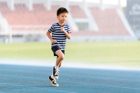 Young Asian boy running on blue track in the stadium during day time to practice himself.