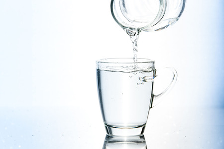 purified: Blue tone of Pouring water in glass on white background