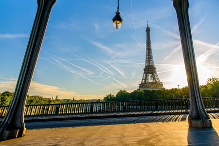 Selective focus at the lamp and pole of Pont de Bir-Hakeim and out focus Eiffel tower as background during the sunrise and light effect. Stock Photo