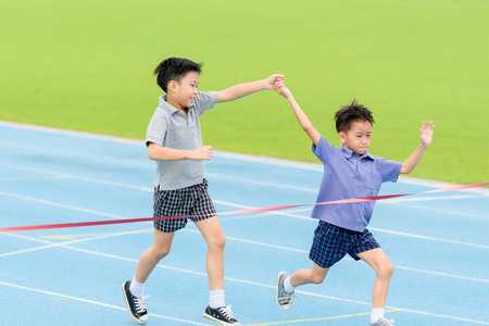 Selective focus at young Asian boy hold hand together running on blue track to the finished line. Stock Photo