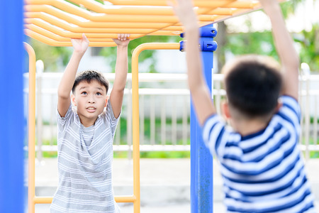 Two young asian boy hang the yellow bar by his hand to exercise at out door playground