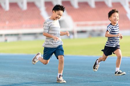 アジアの若い男の子スタジアムで青いトラックの中に一日の時間彼自身を練習します。