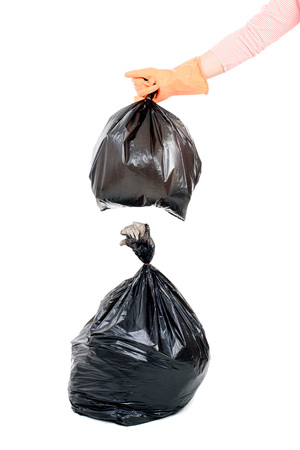 eliminate: Woman hand carry garbage in plastic bag for eliminate on the white background