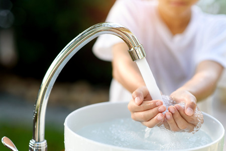 wash: Selective focus and brand new faucet and kid hand taking water.