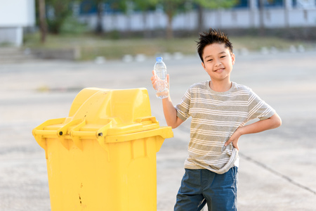 Young Asian boy plastic bottle for eliminate in the yellow bin under the sunlight Stock Photo