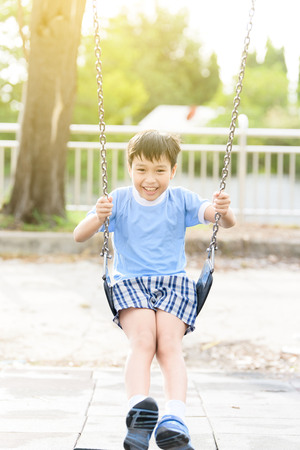 sun energy: young asian boy play a iron chain swinging at the playground under the sunlight in summer