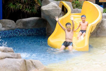 젊은 아시아 태국 소년 여름 시간 동안 공원에서 물 슬라이더를 재생합니다. 스톡 콘텐츠