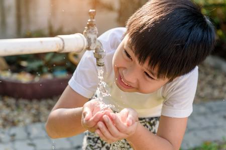 庭の古い蛇口から水を取ってアジアの若い男の子を閉じます。水の不足および干ばつのコンセプト