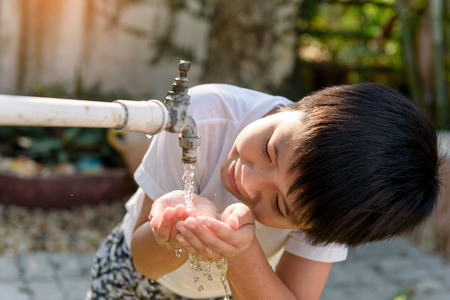 lack of water: Close up young asian boy taking water from old faucet in the garden. Water shortage and drought concept Stock Photo