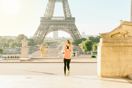 Warm tone and bright sunlight effect of Selective focus at woman running infront of tour Eiffel in the morning. Eiffel tower is the most visit in Paris, France. Stock Photo