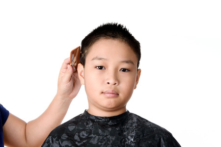 barbershop: Young Asian Thai boy in hair cutting for short and cool design before go to shool, isolated on white background.