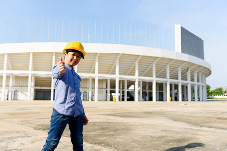 Young asian Thai boy in yellow safety helmet pretend to be engineering during construction area.