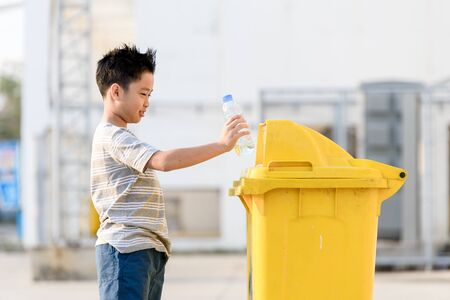 eliminate: Young Asian boy plastic bottle for eliminate in the yellow bin under the sunlight Stock Photo
