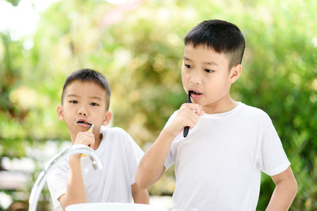 Selective focus at two young Asian boy brushing his teeth in the home garden with out focus green plant background. Foto de archivo