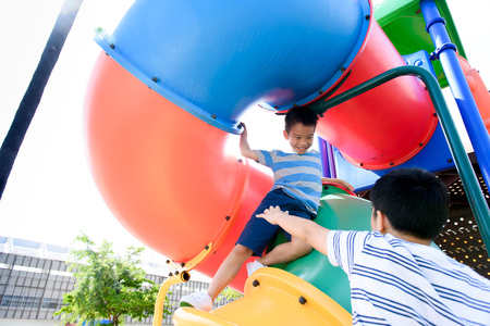 Young asian Thai boy climb to play and pretend fighting on the color full slider playground during summer Stock Photo